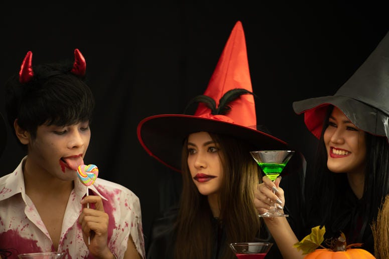 Two witches and a guy licking lollipop
