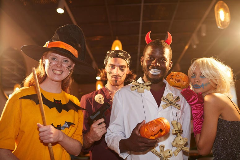 People wearing Halloween costumes posing as witches and pirates