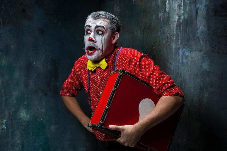 Terrible clown with suitcase and a dark background