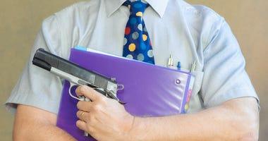 Teacher holding a binder and gun