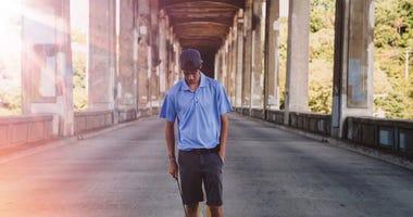 young man balancing ball on golf club