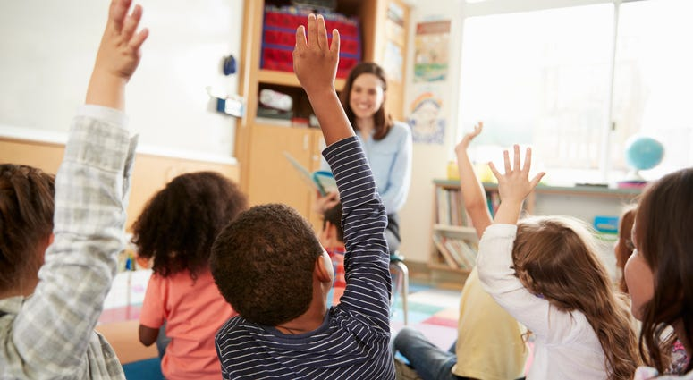 Elementary school children raising their hands in front of their teacher.
