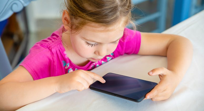 Little girl uses a small touch-screen device.