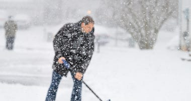 Man in winter coat shoveling driveway during heavy snowstorm.