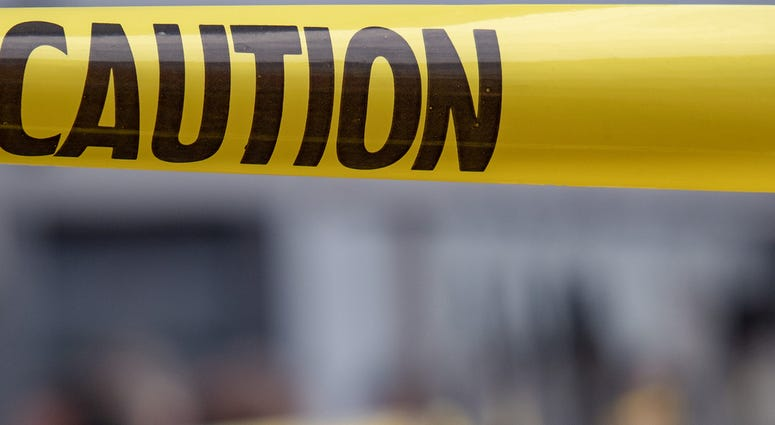 Yellow caution tape is stretched across the site of an emergency.