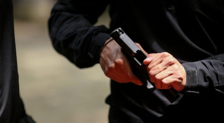 Man operates slide on a semi-automatic handgun