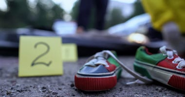 Crime scene with shell casing marker and small child's shoes