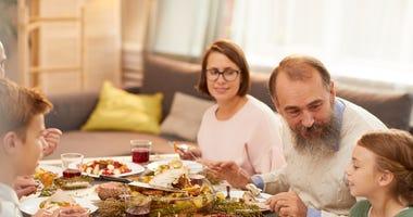 A happy family enjoys Thanksgiving dinner.