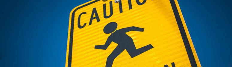 A yellow and black sign warning drivers to be cautious around children