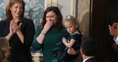 Two-year-old Ellie Schneider is held by her mother, Robin, at the State of the Union Address in the US House Chamber.