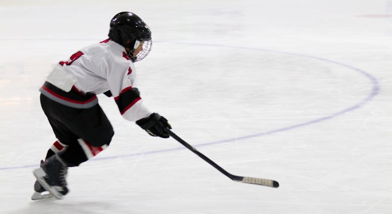 A little boy in a full hockey uniform skates and handles a puck with his stick