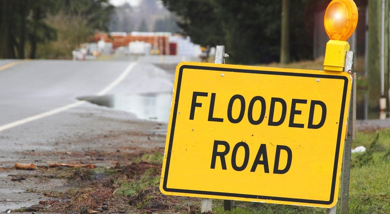 Flooded road sign warns drivers.