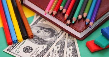 Photograph of school supplies and hundred dollar bills