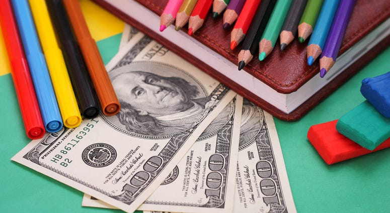 Photograph of school supplies and hundred dollar bills