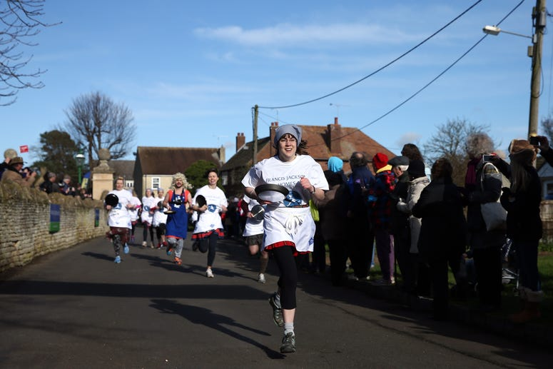 OLNEY, ENGLAND - FEBRUARY 09: Competitors take part in the annual Shrove Tuesday trans-Atlantic pancake race on February 9, 2016 in Olney, England. On Shrove Tuesday every year the ladies of Olney, Buckinghamshire compete in a Pancake Race, a tradition wh