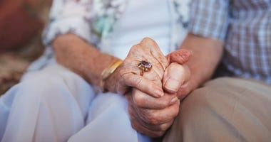 Elderly couple holding hands.