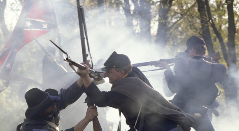 Civil War reenactors fighting with rifles and bayonets.