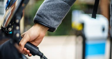 Close-up image of person's hand attaching charger cord to electric vehicle