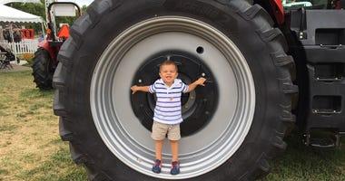 Little E.J. Becker stands inside a big tractor tire.