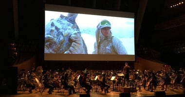 Kansas City Symphony rehearses as Empire Strikes Back plays on movie screen above them