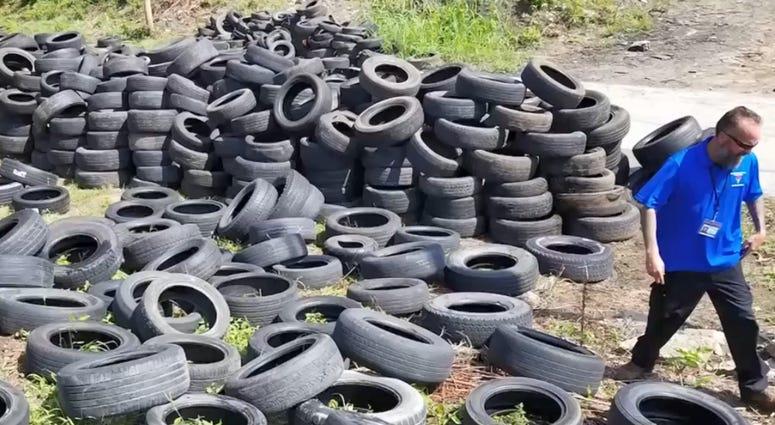 Kansas City illegal dumping investigator walks through a lot containing thousands of tires