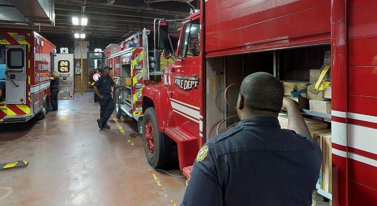 Firefighters standing inside station in Kansas City, Kansas