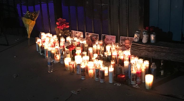 Candles burn outside Tequila KC, where four men were gunned down