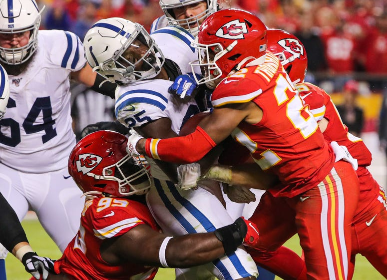 Oct 6, 2019; Kansas City, MO, USA; Indianapolis Colts running back Marlon Mack (25) is tackled by Kansas City Chiefs defensive tackle Khalen Saunders (99) and free safety Juan Thornhill (22) during the second half at Arrowhead Stadium. Mandatory Credit: J