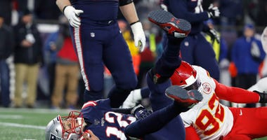 Dec 8, 2019; Foxborough, MA, USA; New England Patriots quarterback Tom Brady (12) tumbles after being sacked by Kansas City Chiefs defensive end Tanoh Kpassagnon (92) during the second quarter at Gillette Stadium. Winslow Townson-USA TODAY Sports
