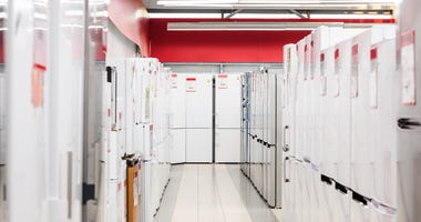 rows of refrigerators in appliance store