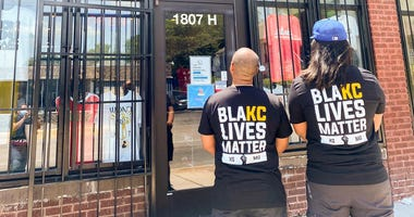 "Two men wear a t-shirt that reads 'BlaKC Lives Matter"", a twiat on the word 'black'"