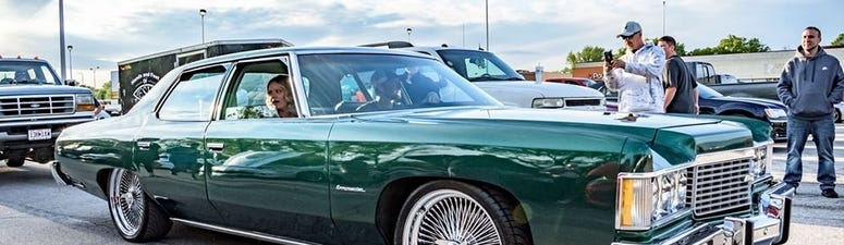 People ride in a classic car during a cruise on Noland Road in Independence, MO