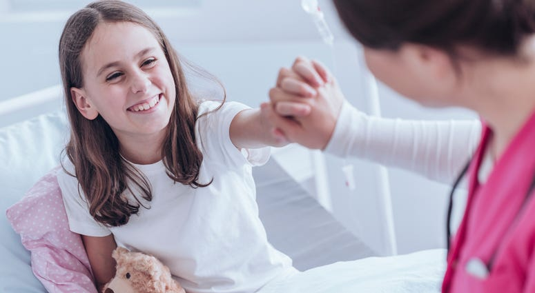 Nurse holding smiling girls hand in hospital bed