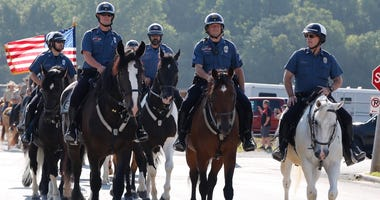 Mounted patrol officers ride their horses.