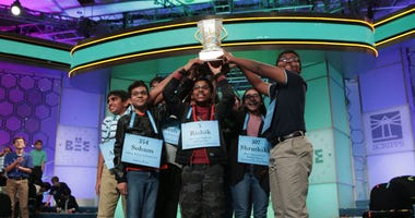 Co-champions of the 2019 scripps national spelling bee raise a trophy.
