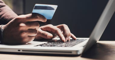 hands holding a credit card to a computer keyboard