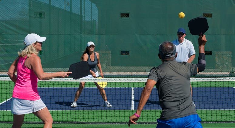 four people play pickleball, a game like tennis with a wiffle ball
