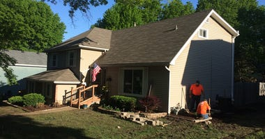 Workers in orange shirts dig next to a home in Overland Park where the Lifetime Network show Military Makeovers is renovating a local military familys home