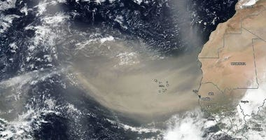 A dust plume seen by satellite moving west off the continent of Africa heading toward North America