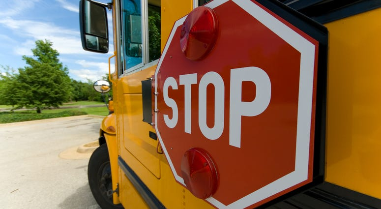 A school bus with a focus on its swing-out stop sign