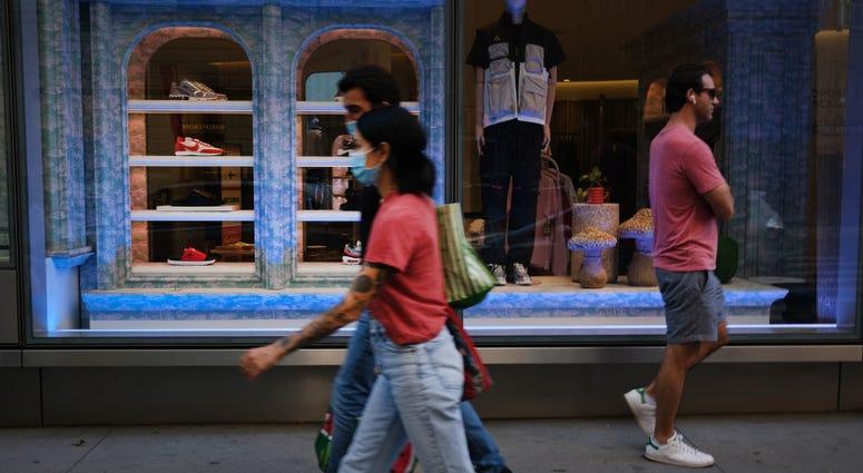 People walking on sidewalk in front of a store