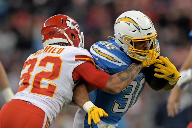 Nov 18, 2019; Mexico City, MEX; Los Angeles Chargers running back Austin Ekeler (30) is tackled by Kansas City Chiefs strong safety Tyrann Mathieu (32) in the first quarter during an NFL International Series game at Estadio Azteca. Kirby Lee-USA TODAY Spo