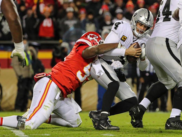Dec 1, 2019; Kansas City, MO, USA; Oakland Raiders quarterback Derek Carr (4) is sacked by Kansas City Chiefs defensive end Chris Jones (95) during the second half at Arrowhead Stadium. Jay Biggerstaff-USA TODAY Sports