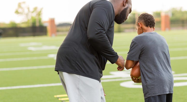 A man coaches a young football player on how to carry the ball