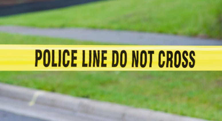 "Yellow crime scene tape in a suburban neighborhood reads, ""Do not cross."""