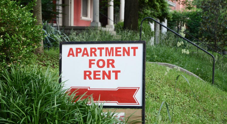 """A sign in a front yard reads, """"Apartment for Rent"""""""