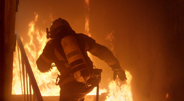 Photograph of firefighter inside a burning building