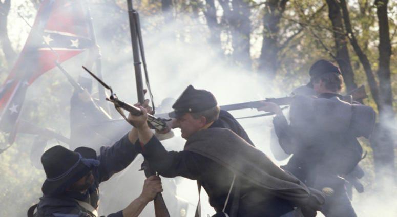 Civil War reenactors fighting with rifles and bayonets.