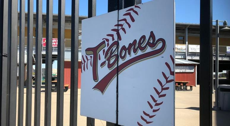 """A sign reading """"T-Bones"""" hangs on the gate of the baseball stadium"""