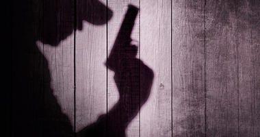 Shadow of a man holding a handgun